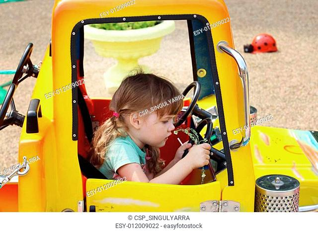 Little cute girl sits at wheel of big yellow toy car at sunny da