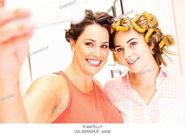 Two female friends, foam rollers in hair, taking selfie with smartphone