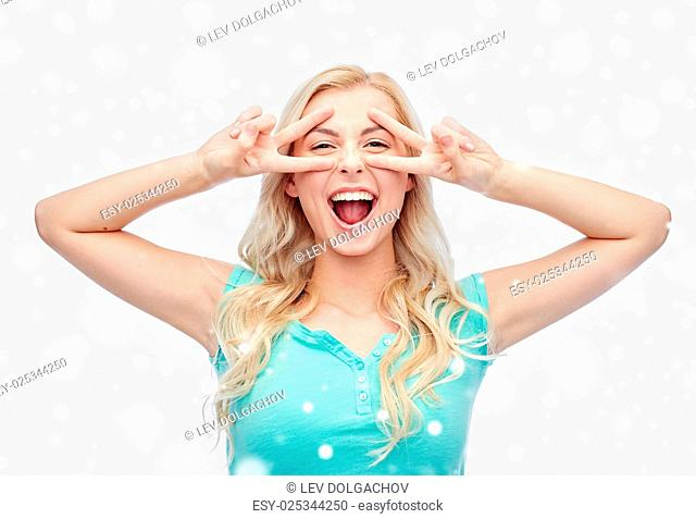 positive gesture, emotion, winter holidays, christmas and people concept - smiling young woman or teenage girl showing peace hand sign with both hands over snow