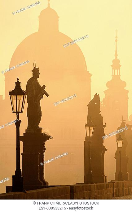 charles bridge prague at dawn during foggy morning