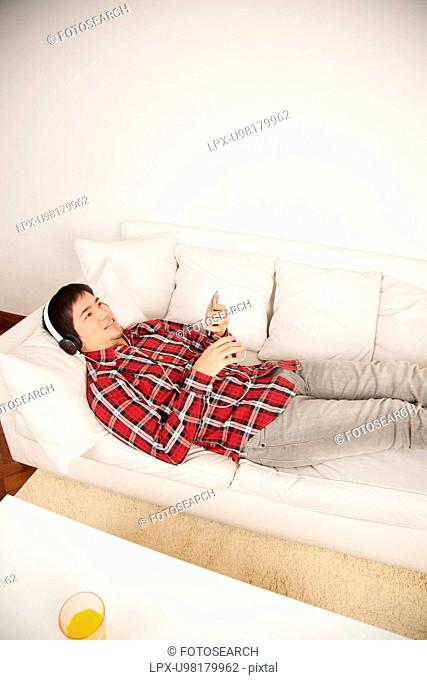 Man listening to music and lying