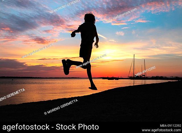 9 year old girl on summer vacation, plays by the sea at sunset on Vrsi Mulo beach, Vrsi, Zadar county, Dalmatia, Croatia