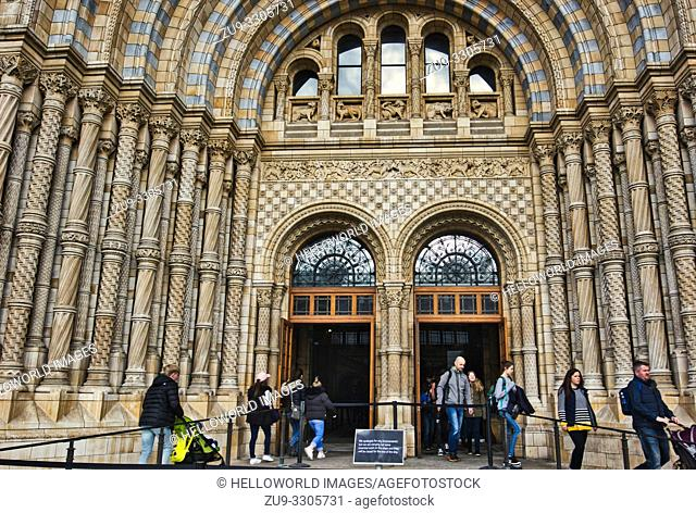 Tourists entering and leaving through the ornate terracotta main entrance to the Natural History Museum, South Kensington, London, England