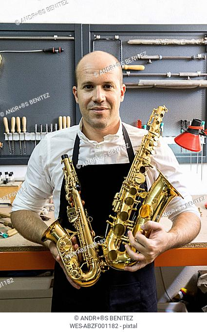 Portrait of an instrument maker holding two saxophones in his workshop