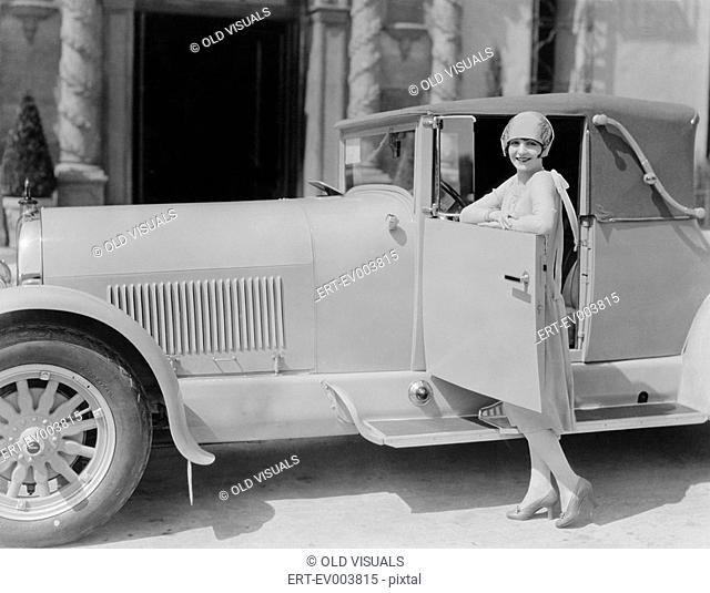 Portrait of woman posing with car All persons depicted are not longer living and no estate exists Supplier warranties that there will be no model release issues