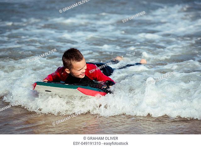 Little Boy Bodyboarding in the Sea