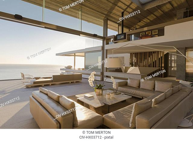 Sunny modern, luxury home showcase interior living room open to ocean view