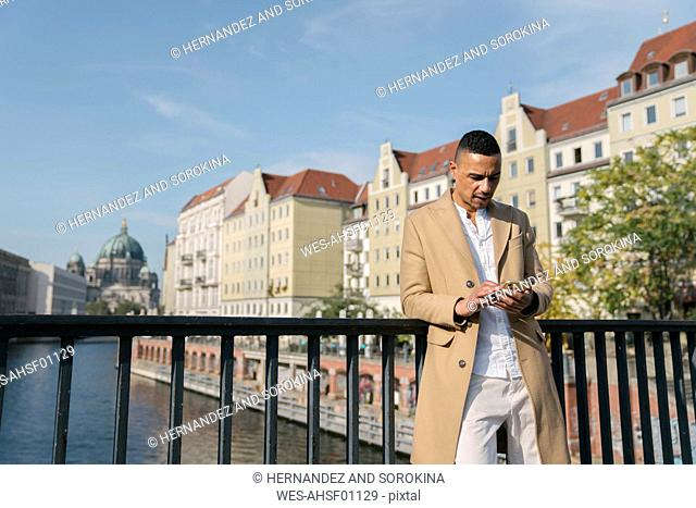 Businessman standing on a bridge looking at smartphone, Berlin, Germany