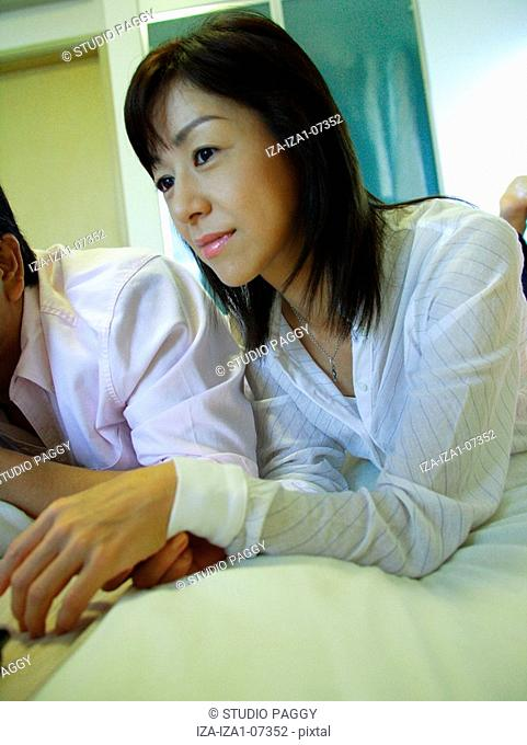 Mid adult couple lying on the bed and using a laptop