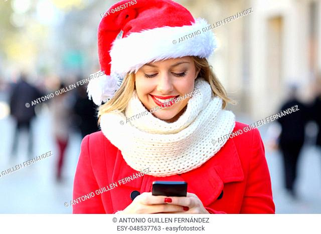 Front view of a happy woman sending phone text on christmas in the street