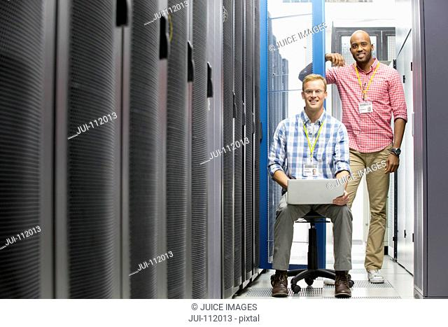 Technicians with laptop looking at camera and checking server in data centre