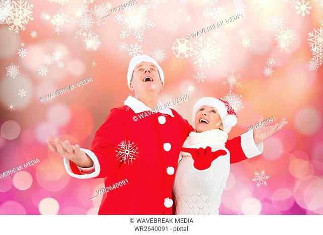Happy couple in santa costume pretending to catch snowflakes
