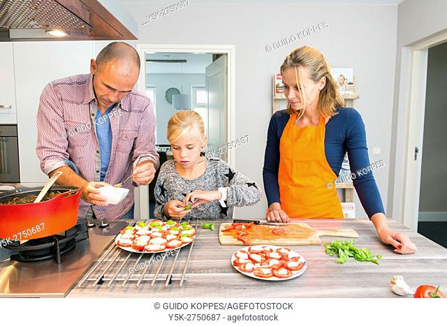 Kaatsheuvel, Netherlands. Mid adult man and woman preparing tomatoes for a sidedish with Lasagna dish dinner, assisted by their young daughter