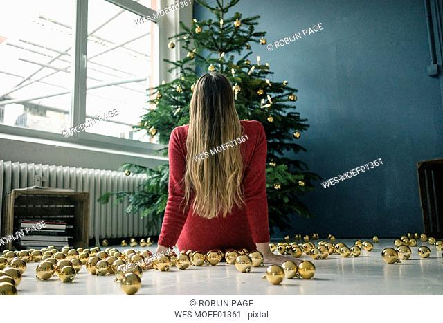 Back view of woman sitting on the floor with many golden Christmas baubles looking at Christmas tree
