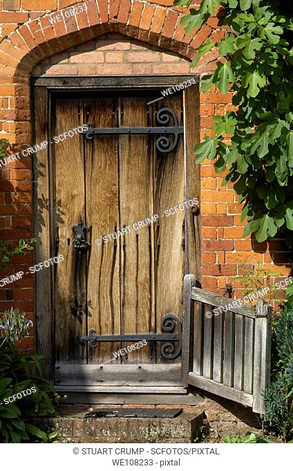 Traditional Old Wooden Door in an English Cottage Garden, England, United Kingdom