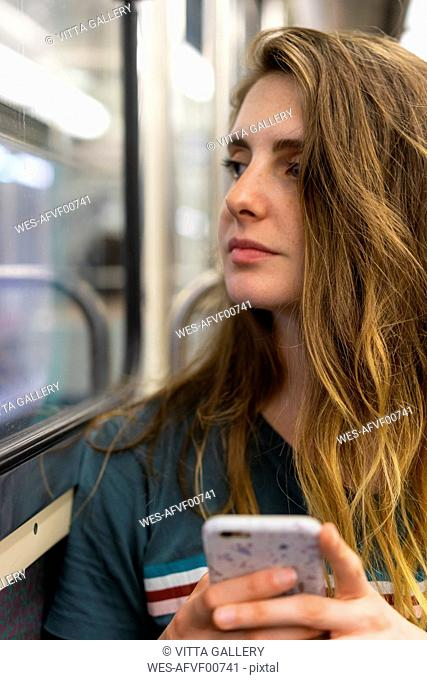 Portrait of young woman with smartphone in underground train