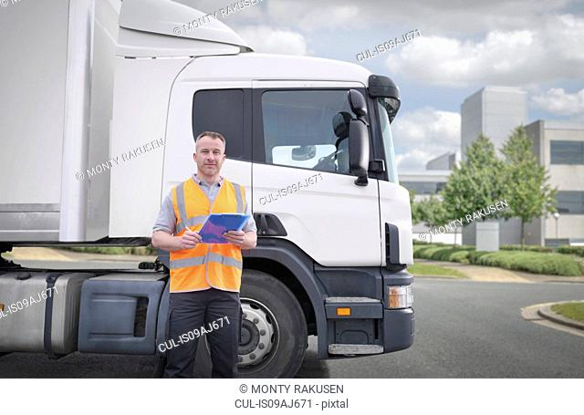 Portrait of truck driver standing by truck