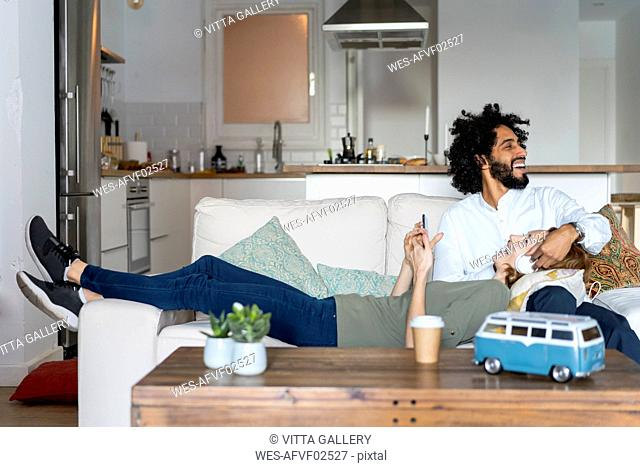 Couple relaxing on couch, planning their road trip