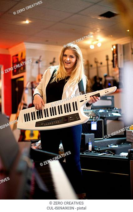 Young woman playing keytar in music store