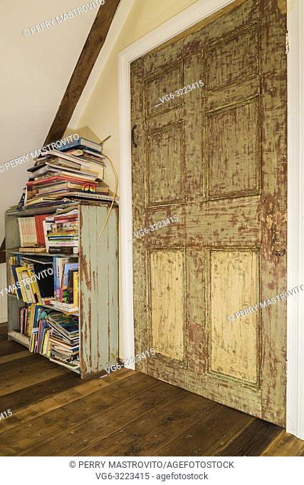 Attic room with antique wooden bookcase next to stressed finish closet door inside an old 1835 fieldstone house