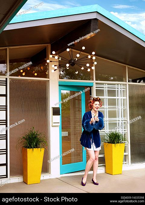 Vintage-styled woman standing outside the door of her mid-century home smiling