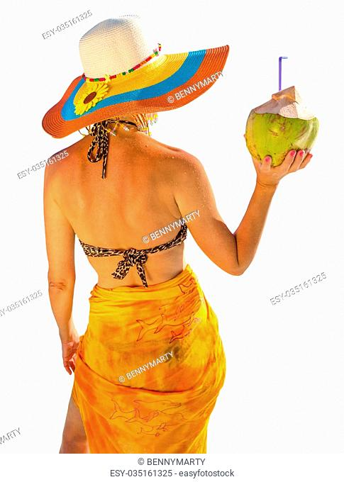 Rear view of attractive and tanned woman with yellow sarong and wide-brimmed hat while holding a coconut fresh cocktail. Isolated on white background