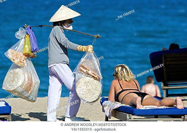 Conical hat woman selling snacks on beach Nha Trang resort Vietnam