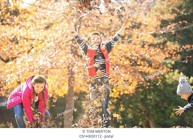Playful boys and girl running and jumping in autumn leaves