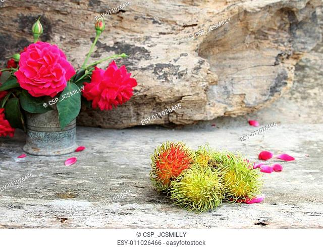 Still life with rambutan Thai fruit and rose on wooden background