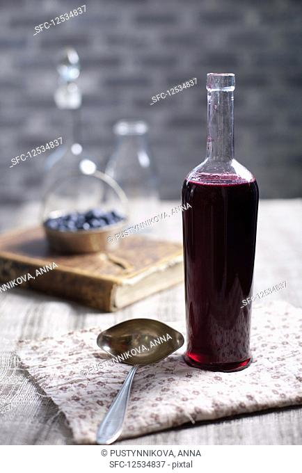 Old, vintage wine bottle with homemade blackcurrant, blueberry and blackberry vinegar