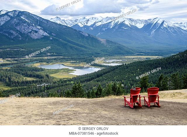 Two red chairs on a flat mountain slope are inviting to sit and enjoy the beautiful view of a green valley near the Banff city, Canada