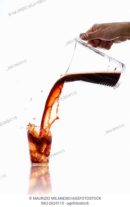 Drink, vigorously poured from a carafe, overflowing splashing from a glass, on a white background