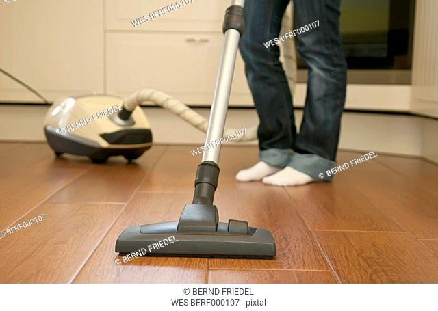 Germany, Brandenburg, Young woman cleaning floor with vacuum cleaner