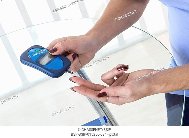 Woman checking her blood glucose level