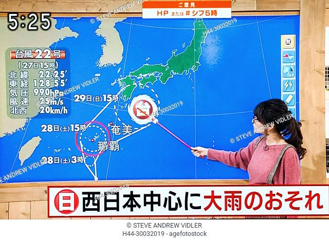 Japan, Japanese TV Weather Forecaster Indicating Path of Approaching Typhoon