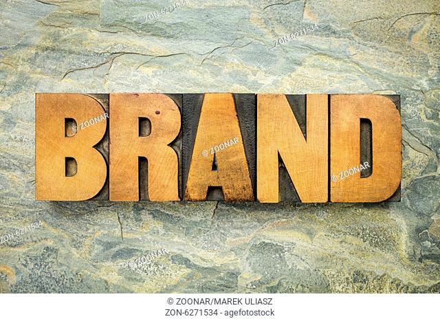 brand - a word in vintage letterpress wood type on a green slate rock background