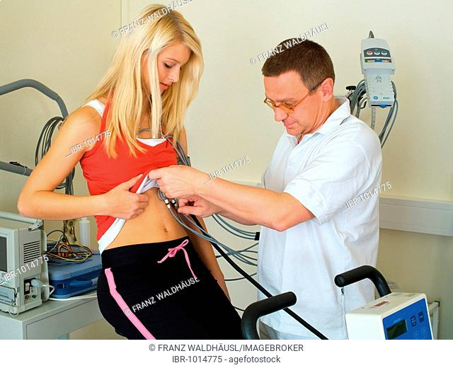 Doctor conducting an ergometer test in a medical practice with a young woman