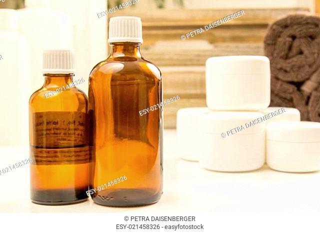 Glasflasche, Creme und Handtücher