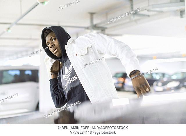 fashionable man with adidas shirt walking in parking garage, in Munich, Germany