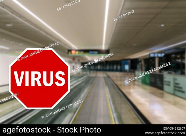 Wuhan coronavirus pandemic concept with STOP sign with the word virus superimposed against unidentifiable purposely left out of focus empty airport terminal