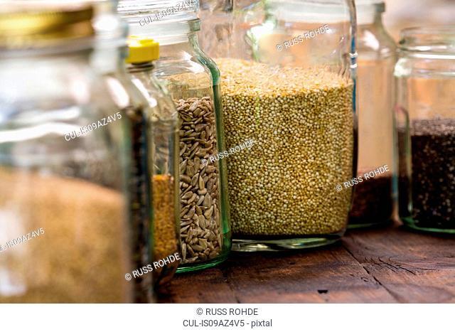 Jars of quinoa, sunflower, linseed on table