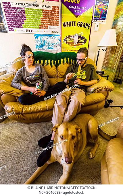 Young people smoking marijuana and relaxing at home, Aurora, Colorado USA. Colorado was the first state to legalize the sale of marijuana for recreational use...