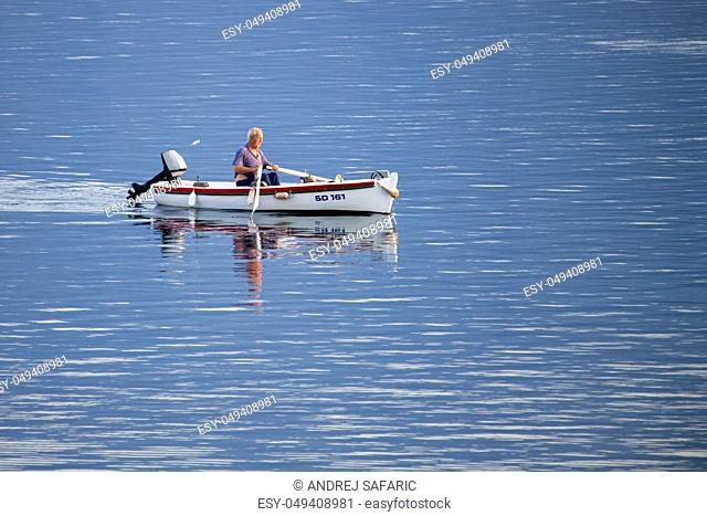 Old traditional fisherman in Croatia on a small wooden boat catching fish and rowing back into the harbor, authentic, not staged, early morning