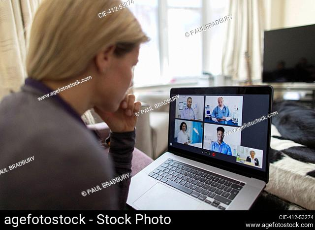 Woman video chatting with doctors at laptop from home