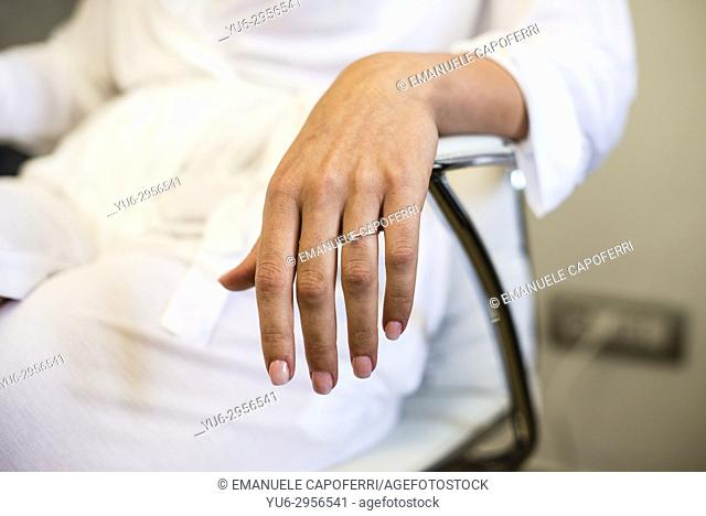 hand of woman with finger a diamond ring, sitting on a chair