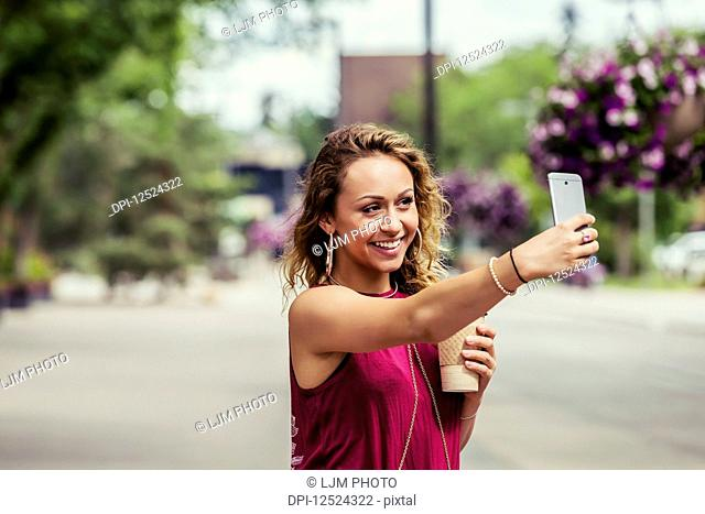 A young beautiful woman takes a self-portrait on a cell phone on a street near a university campus; Edmonton, Alberta, Canada