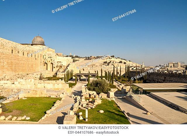 This is a view of the Mount of Olives from the Temple Mount. A portion of the wall around the old city of Jerusalem is visible in the center with the two arches
