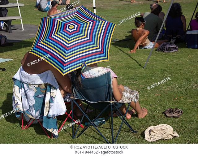 two people in camping chairs from behind in a park at a concert with a striped sun umbrella