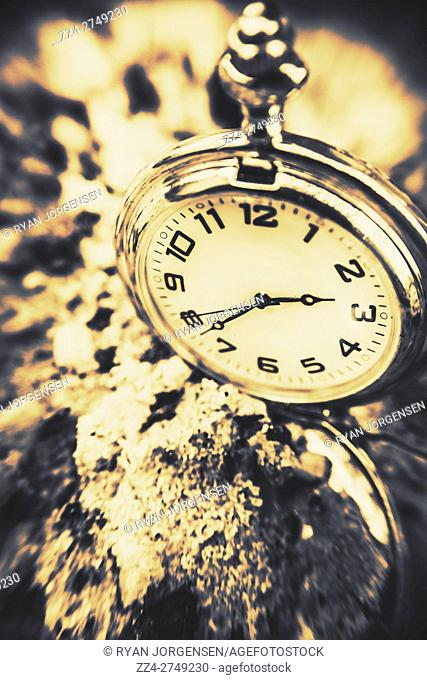 Vintage still-life antiques photo on a classical styled pocket clock or pocketwatch laying buried in a sandy illustion of time