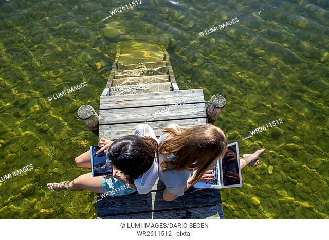 Two young women sit on pier by lake using tablet and laptop